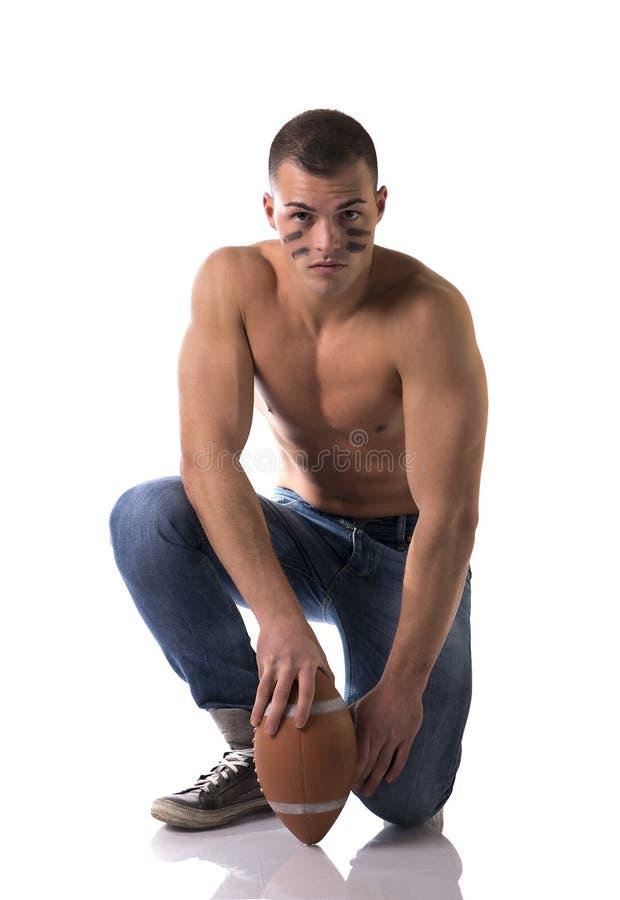 Shirtless Amerikaanse voetbalster in jeans met bal het knielen royalty-vrije stock foto's