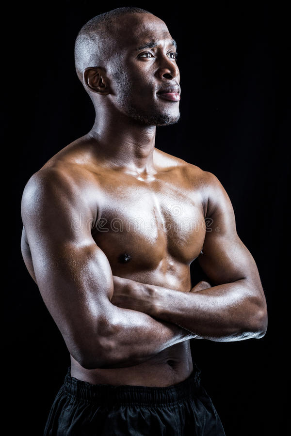 Shirtless athlete standing with arms crossed while looking away. Against black background stock photography