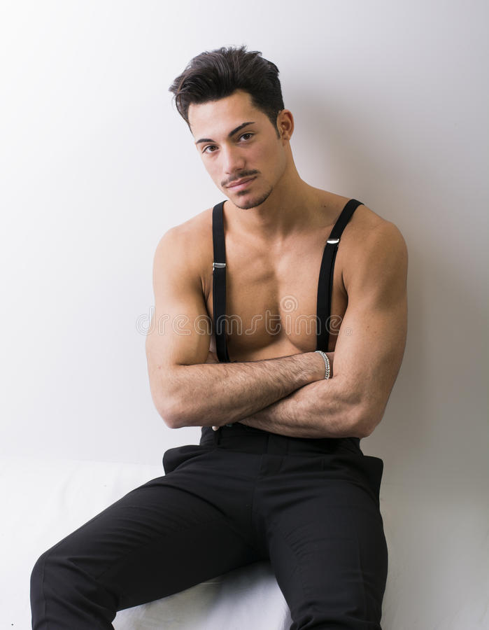 Shirtless athletic young man with suspenders and black pants. Arms crossed royalty free stock image