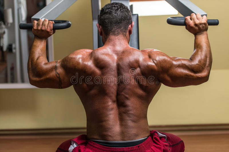 Shirtless body builder doing military press for shoulder. Shirtless bodybuilder doing military press for shoulder royalty free stock image