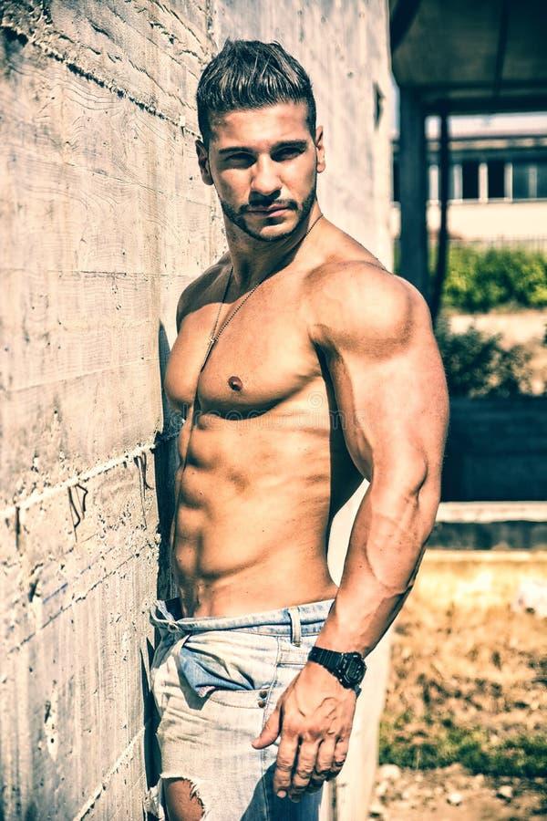 Shirtless bodybuilder tegen concrete muur stock afbeelding
