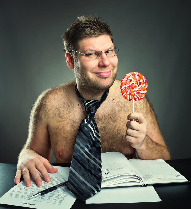 Shirtless businessman. With big lollipop stock image