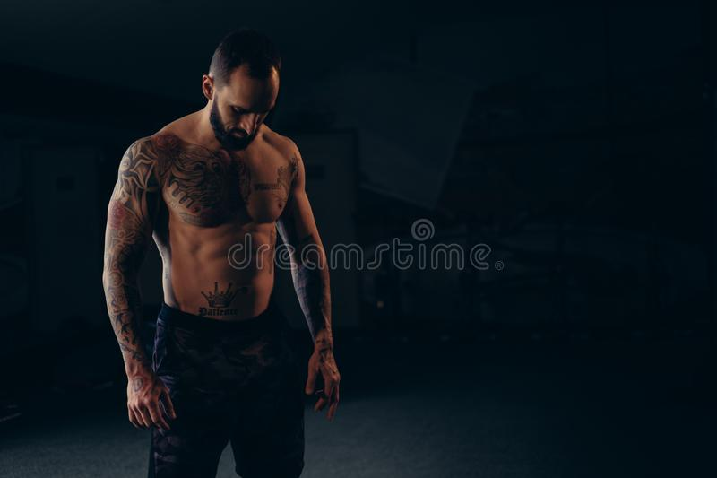 Shirtless concentrated male athlete looking to the floor stock photo