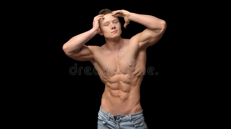 Shirtless, fitness shaped muscular men with perfect sporty body only in jeans with arms raised to a head posing at black royalty free stock photo
