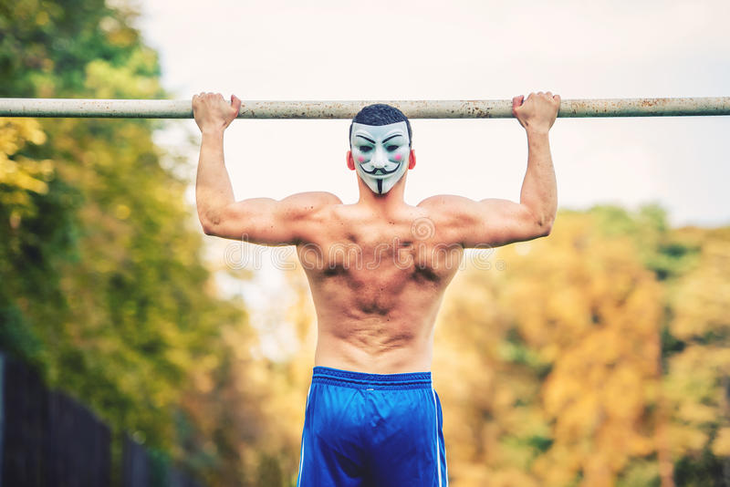 Shirtless handsome man doing chin ups in park, wearing an anonymus mask. Fitness player, personal trainer working out in park royalty free stock images