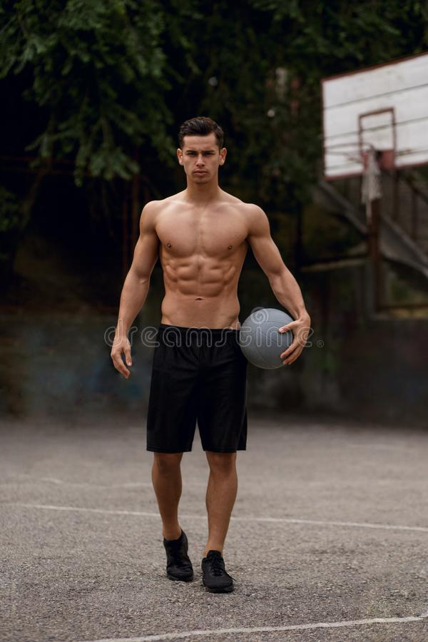 Shirtless, idrotts- muskul?s grabb med bollen i h?nder som sitter p? en basketdomstol, p? en gatabakgrund royaltyfri fotografi