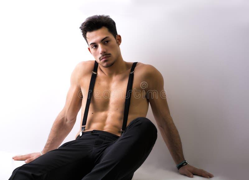 Shirtless idrotts- ung man med hängslen som sitter på golv arkivbilder