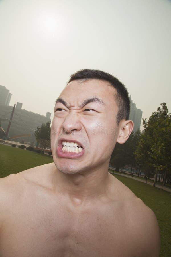 Shirtless jonge atletische mens die in openlucht in een park in Peking grommen royalty-vrije stock afbeelding