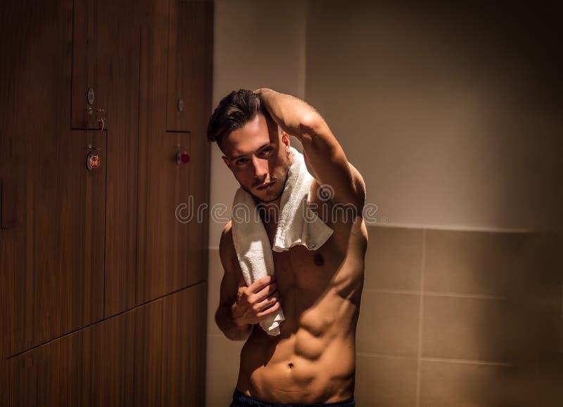 Shirtless jonge mannelijke atleet in gymnastiekkleedkamer met handdoek stock afbeelding