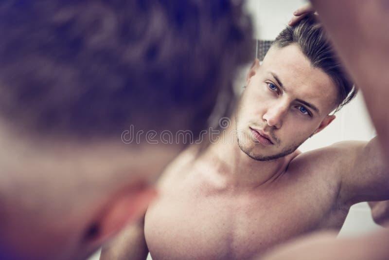 Shirtless jonge mens die zijn gezicht in badkamersspiegel onderzoekt royalty-vrije stock afbeeldingen
