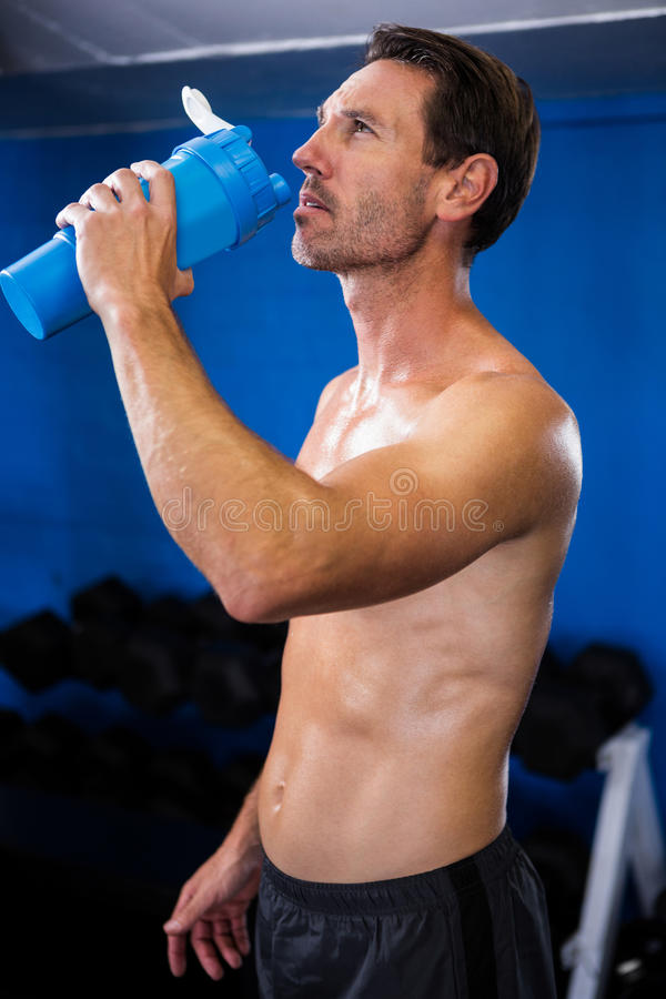 Shirtless jonge mensen drinkwater in gymnastiek stock foto