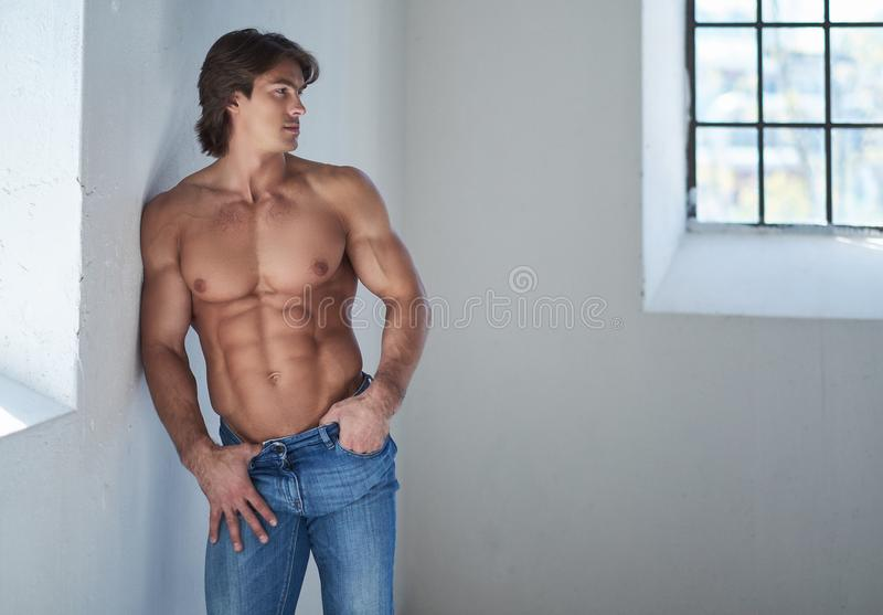Shirtless knap mannetje met een perfect spierlichaam die op een muur in de studio leunen, die een venster bekijken royalty-vrije stock foto's
