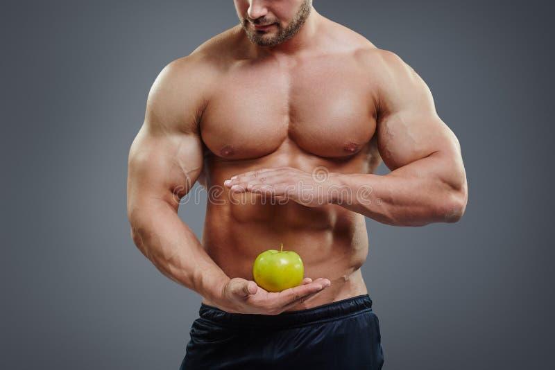 Shirtless kroppsbyggare som rymmer ett äpple i hans händer royaltyfri foto
