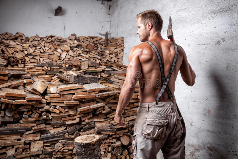 Shirtless lumberjack with an axe. Shirtless handsome and muscular lumberjack with an axe royalty free stock images