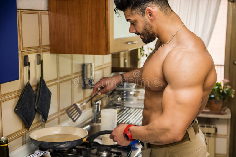 Shirtless male bodybuilder cooking in kitchen stock images