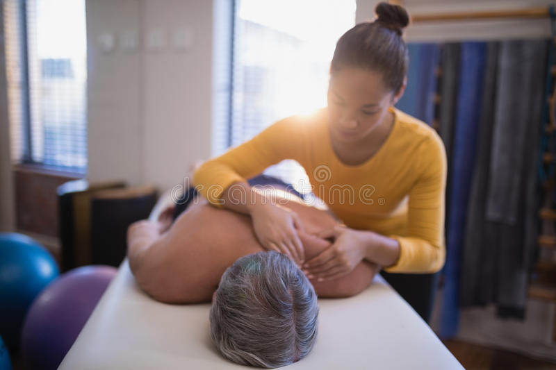 Shirtless male patient lying on bed receiving neck massage from female therapist. At hospital ward stock image