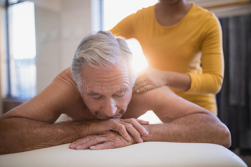 Shirtless male patient lying on bed receiving neck massage from young female therapist royalty free stock images