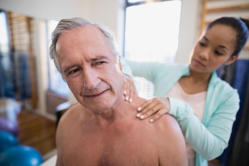 Shirtless male patient receiving neck massage from female therapist. At hospital ward royalty free stock image
