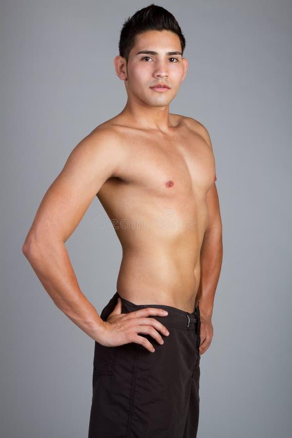 Shirtless Man. Wearing swim trunks royalty free stock photo