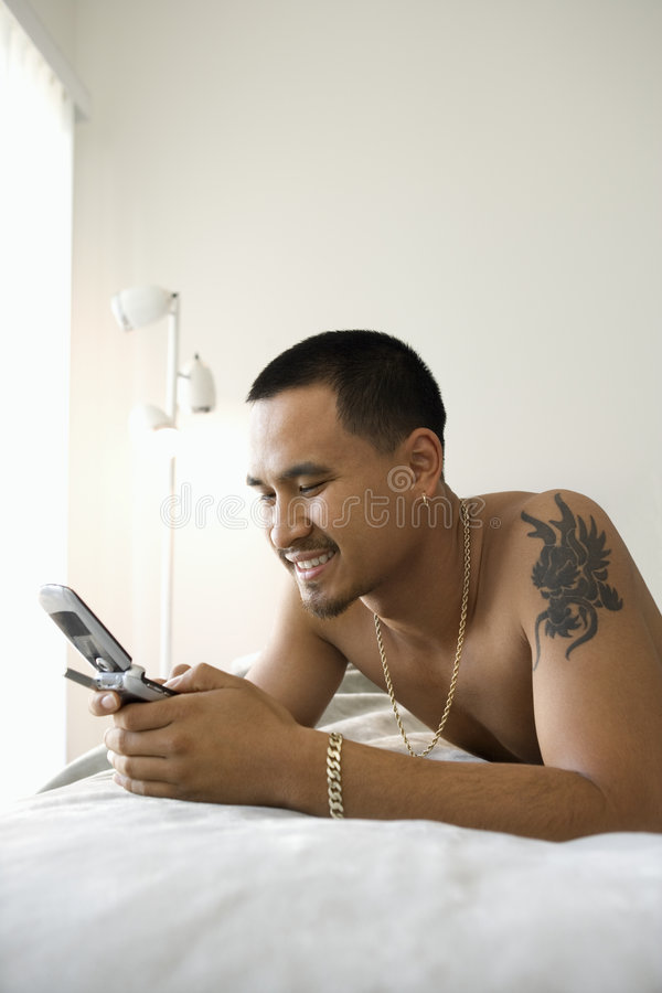 Shirtless man on bed using cellphone. royalty free stock images