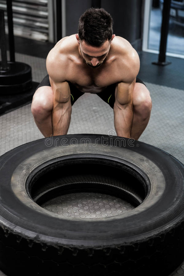 Shirtless man flipping heavy tire royalty free stock images