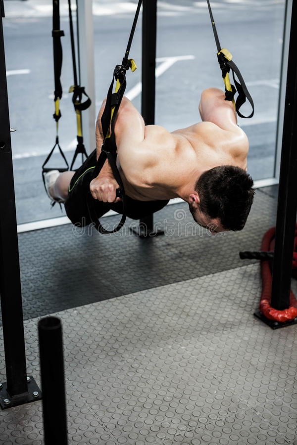 Shirtless man hanging at the rope. At the crossfit gym stock photo