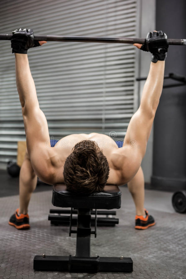 Shirtless man lifting heavy barbell on bench. At the crossfit gym royalty free stock images