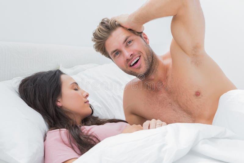 Shirtless Man Posing Next To His Sleeping Partner Royalty Free Stock Photos