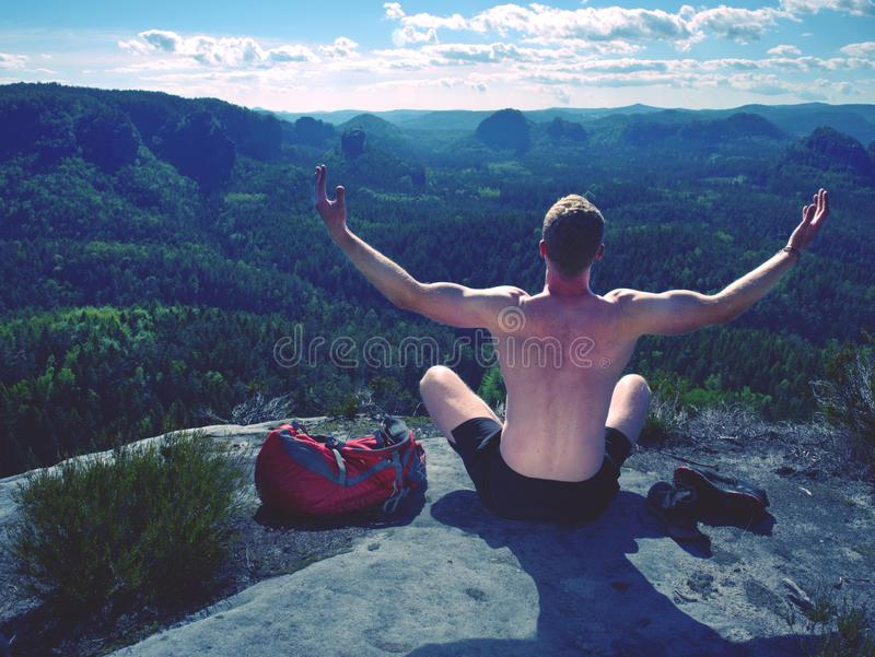 Shirtless man relaxing meditation with serene view mountains stock image