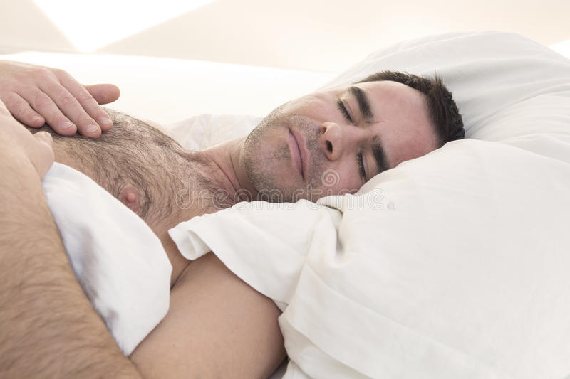 Shirtless man sleeping in bed stock photography