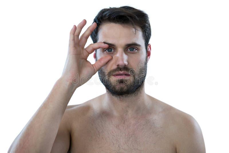 Shirtless man som öppnar hans öga med fingrar arkivfoton