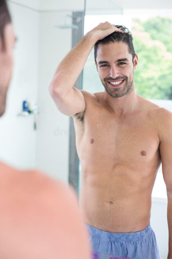 Shirtless man som ler, medan se i spegel royaltyfria bilder