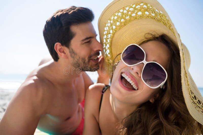 Shirtless man som viskar det gladlynta kvinnaörat på stranden arkivfoton