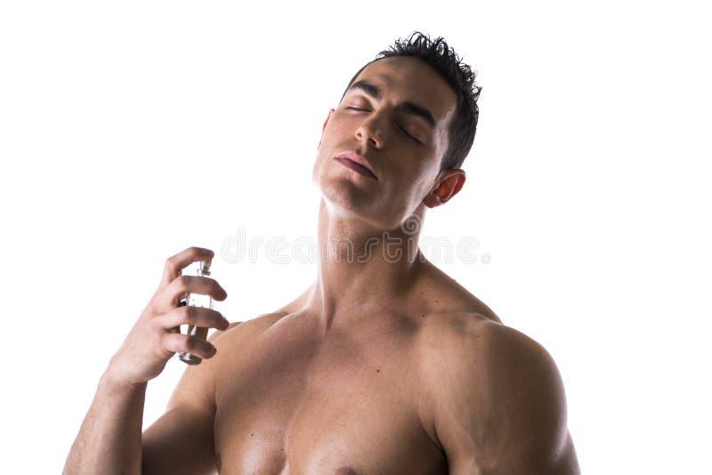 Shirtless manlig modell som besprutar eau-de-cologne royaltyfria foton