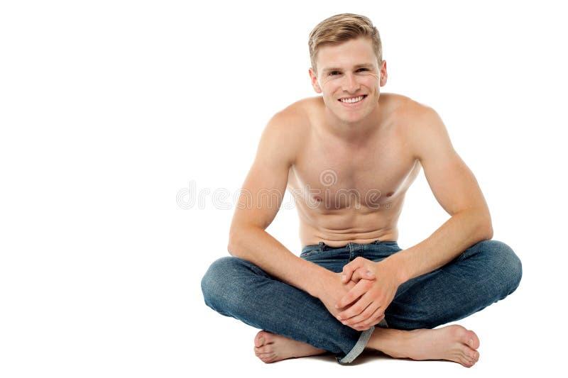 Shirtless mansammanträde på golvet fotografering för bildbyråer
