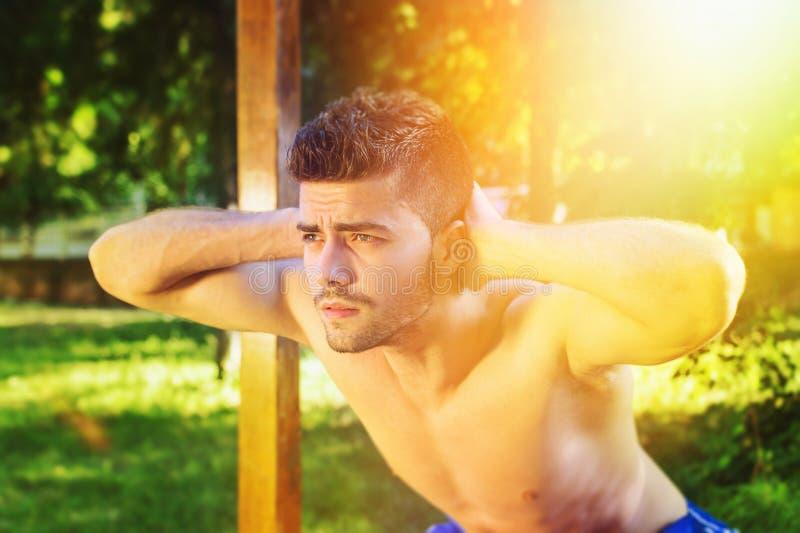 Shirtless mens die hurkzit in openlucht op zonnige de zomerdag doen royalty-vrije stock afbeeldingen