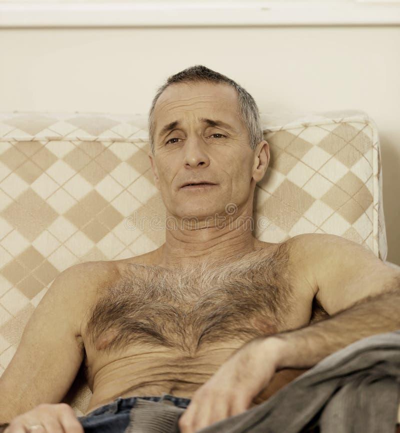 Shirtless mensenzitting op een bank royalty-vrije stock afbeelding