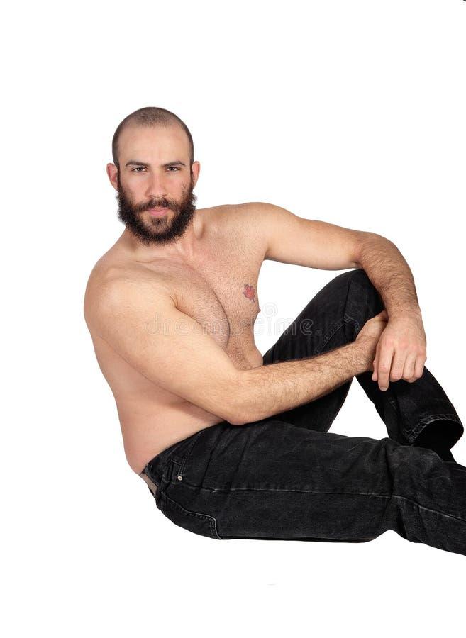 Shirtless mensenzitting op vloer het ontspannen stock afbeelding