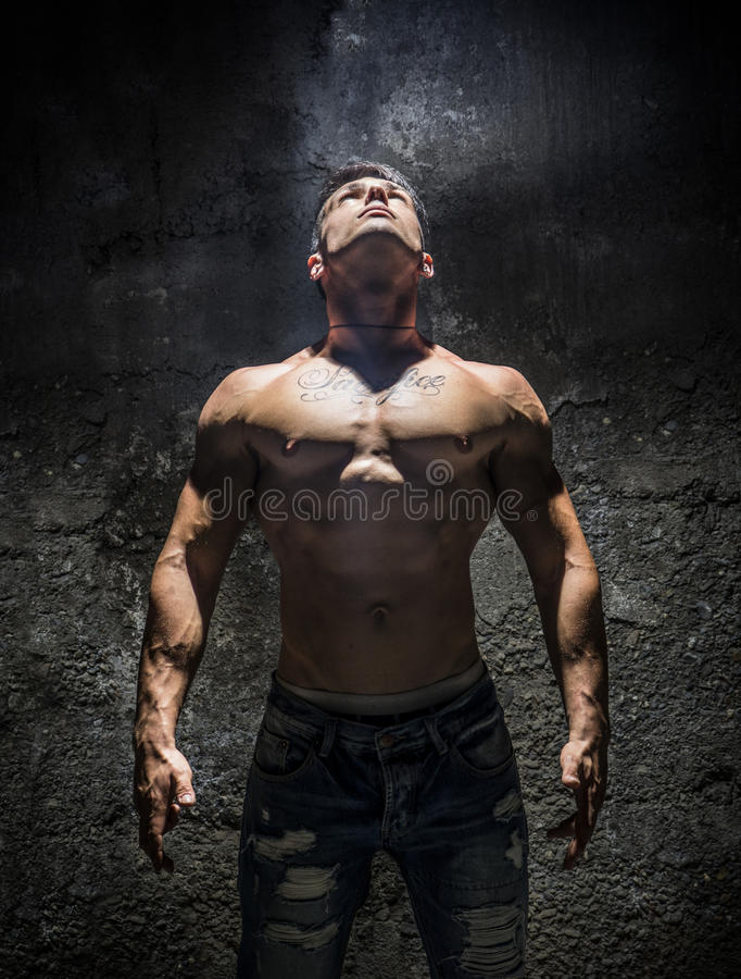 Shirtless Muscle Man Looking Up Into Bright Overhead Light. Illuminating Him Like a Superhero royalty free stock image