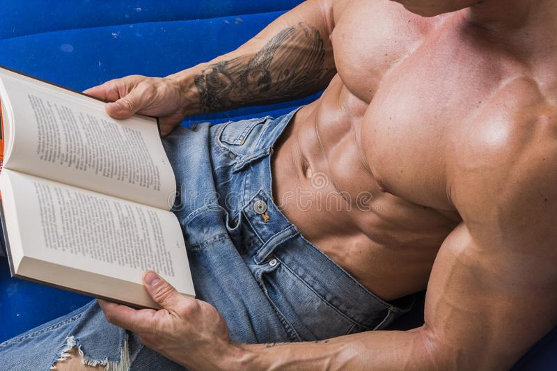 Muscular bodybuilder man reading book. Shirtless muscular bodybuilder man reading book while laying on couch stock photo