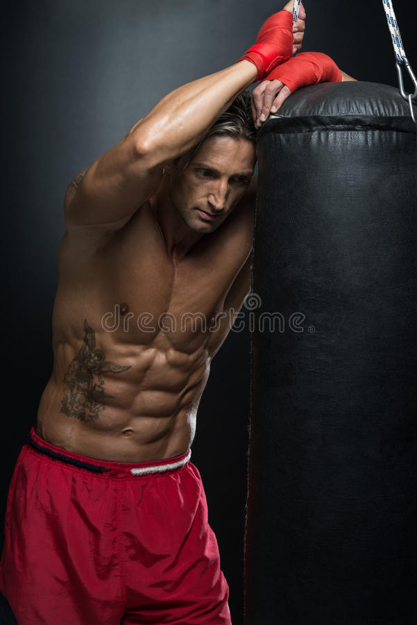 Shirtless Muscular Boxer With Punching Bag In Gym royalty free stock images