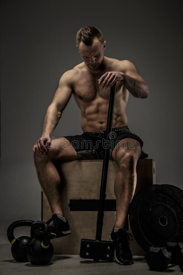 Muscular man on wooden box. Shirtless muscular man sitting on wooben box and holding big black hummer stock photo