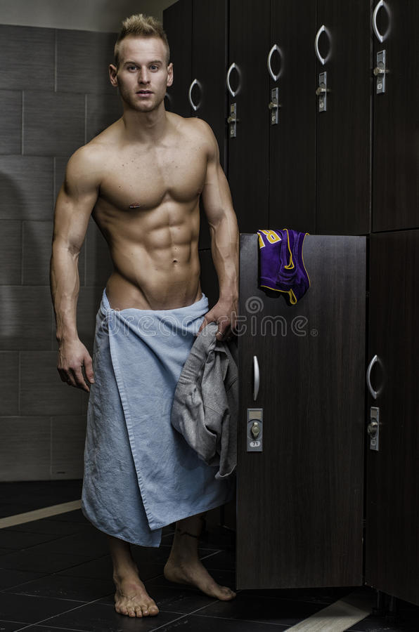 Shirtless muscular young male athlete in gym. Dressing room, smiling with towel around waist royalty free stock photography