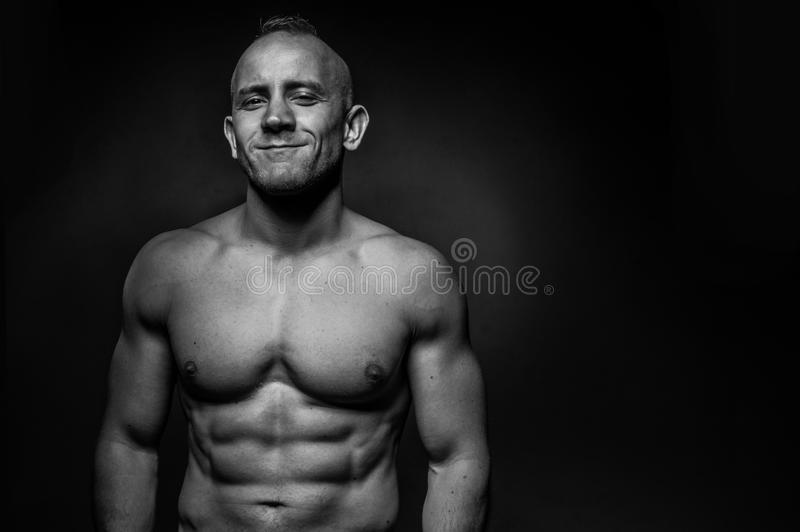 Shirtless muskulös man med ett karismatiskt leende arkivbild