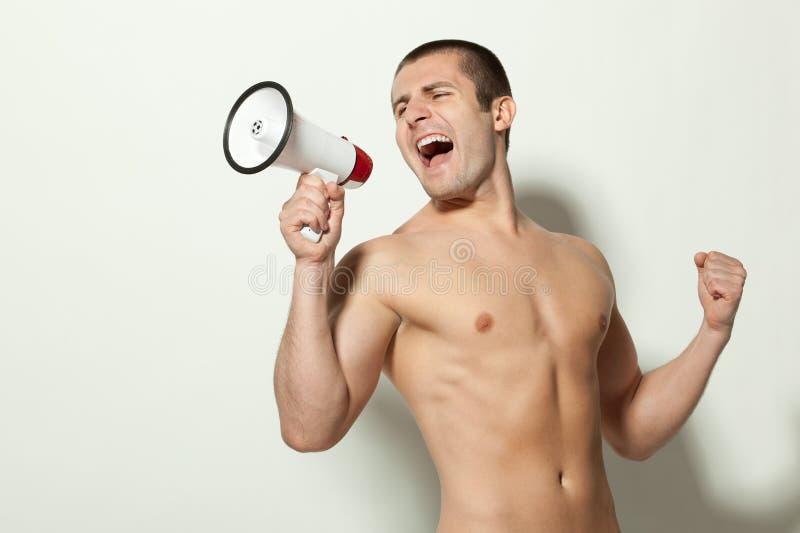 Shirtless muskulös man som skriker in i megafonen arkivbild