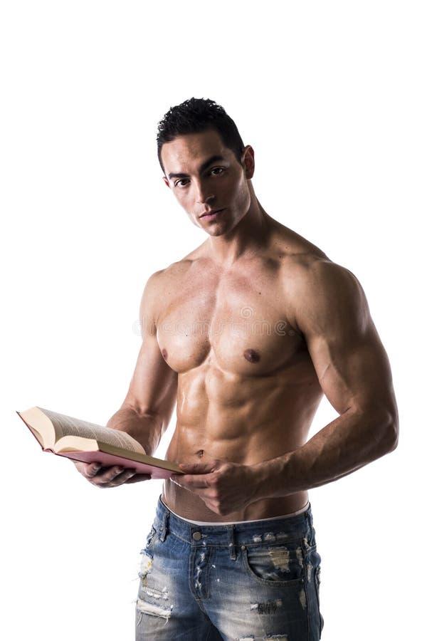 Shirtless muskulös sexig man som läser den stora boken royaltyfria foton