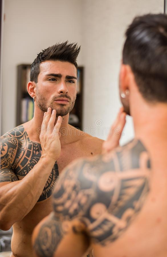 Shirtless muskulös stilig man i sovrum vid spegeln arkivfoto