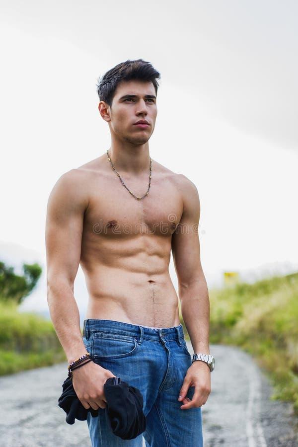 Shirtless muskulös ung man som går på den lantliga vägen royaltyfria foton