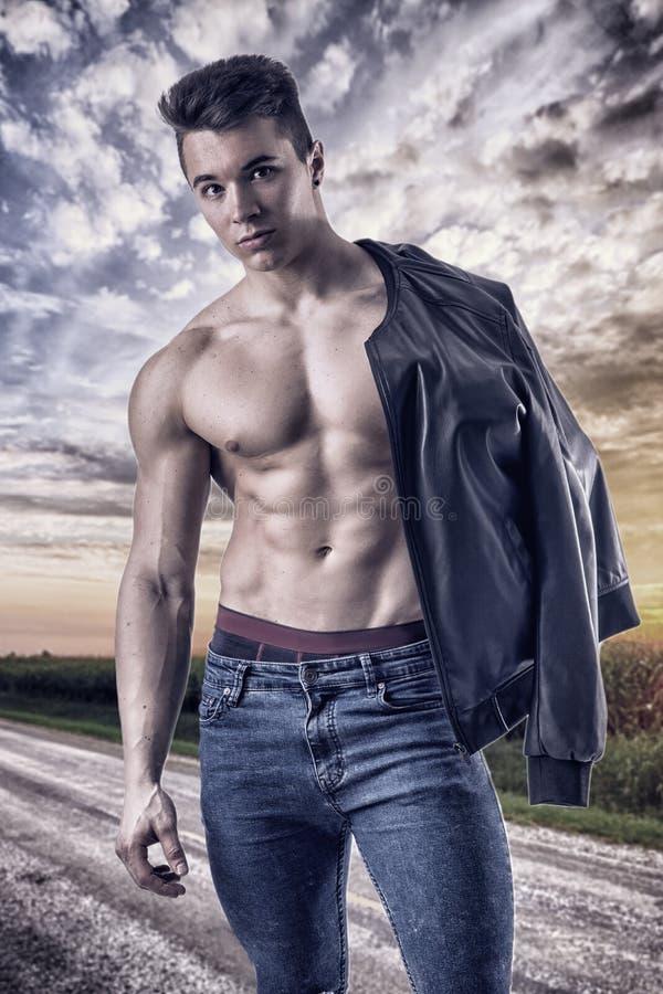 Shirtless muskulös ung man som går på den lantliga vägen arkivfoton