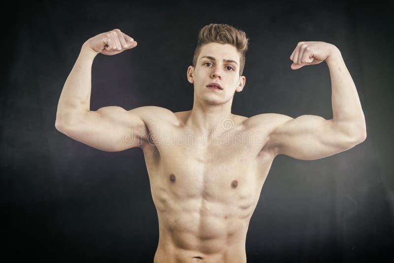 Shirtless muskulös ung man som gör dubbel biceps royaltyfria foton